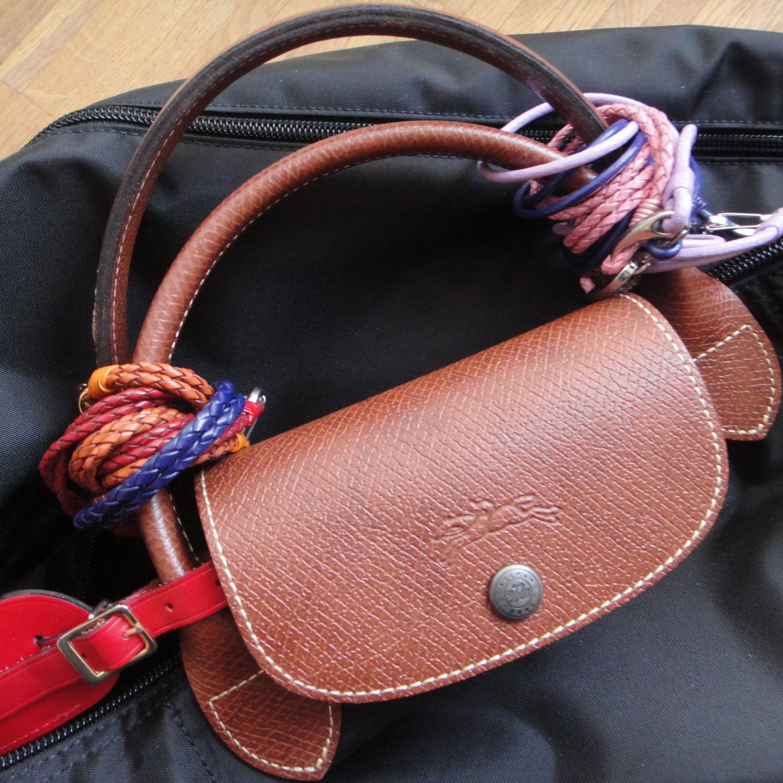 bracelets tied to my carry-on / Armbänder an meiner Reisetasche