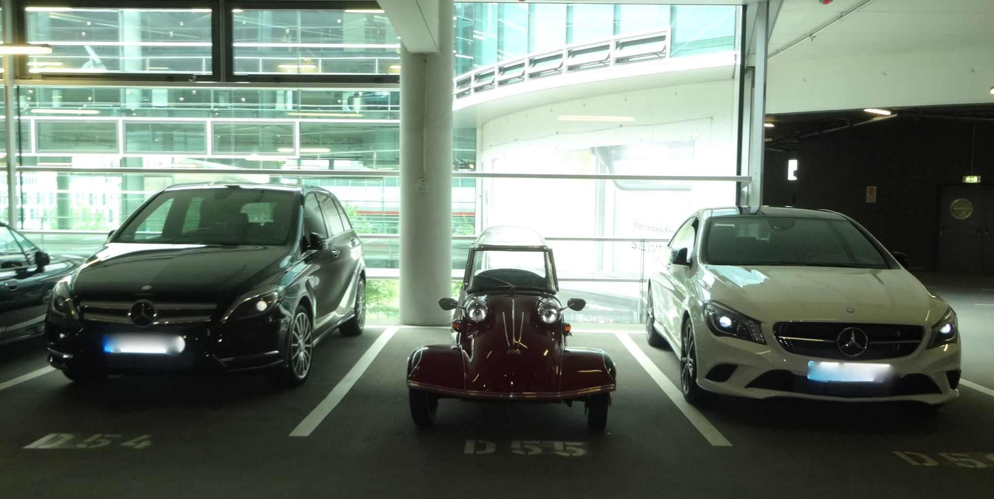 a Messerschmitt 3-wheeler between two large Mercedes cars