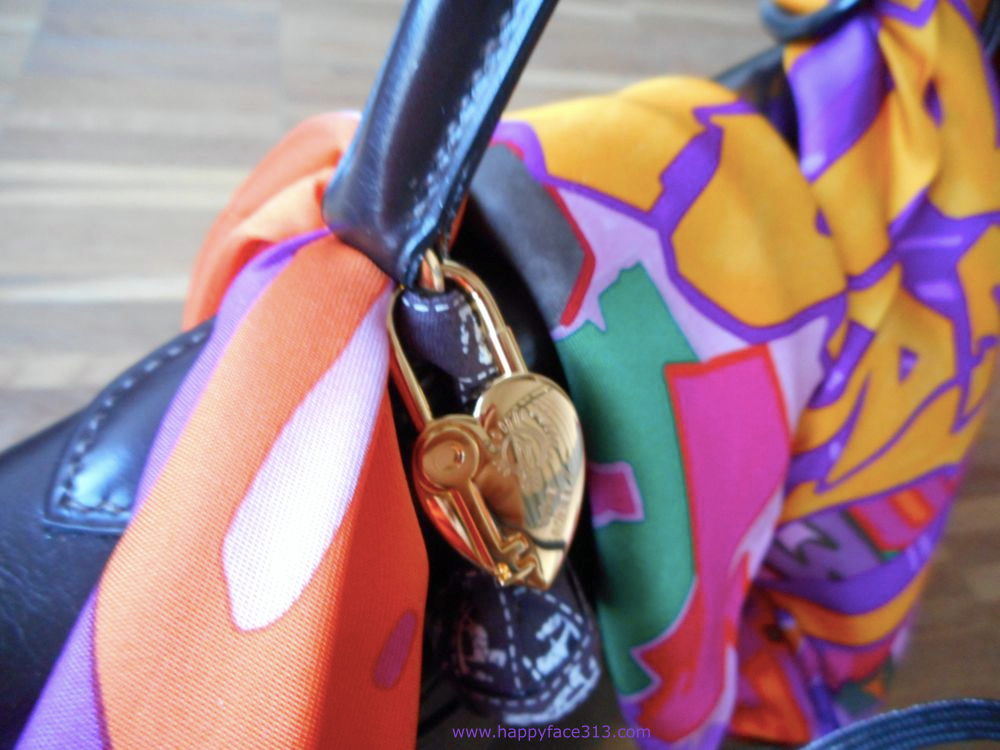 securing Hermès scarf with a knot, heart bag charm